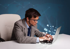Young man sitting at dest and typing on laptop with message icon Stock Photography