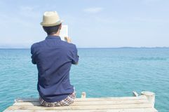 Young man sitting on the dock reading a book. Young man in blue shirt sitting on the dock reading a book stock images