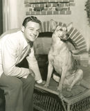 Young man sitting with dog at home Royalty Free Stock Photography