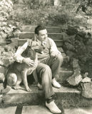 Young man sitting with dog on steps outdoors Royalty Free Stock Photo