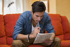 Young man sitting doing a crossword puzzle Royalty Free Stock Photos