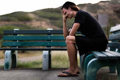 Young man sitting down depressed with his hands over face. Depressing scene. Outdoor park bench. Man trying to figure out what to do Stock Image