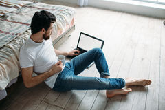 Young man sitting down on the floor near the bed Royalty Free Stock Image
