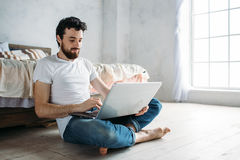 Young man sitting down on the floor near the bed. With folded legs. Nice cute guy is working or watching interesting video on the laptop. He is smiling Royalty Free Stock Images