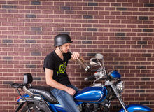 Young man sitting drinking alcohol on his bike Stock Image