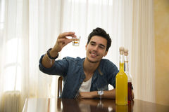 Young man sitting drinking alone at a table, making a toast Royalty Free Stock Photo