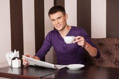 Young man sitting and drinking coffee. Stock Photography