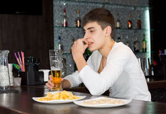 Young man sitting drinking and eating at a pub Royalty Free Stock Images