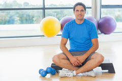 Young man sitting with dumbbells in fitness studio Royalty Free Stock Photo