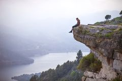 Young man sitting on edge of cliff and looking at river stock image