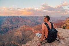 Young man sitting at the edge of the Grand Canyon. On the island of Kauai, Hawaii Royalty Free Stock Photos