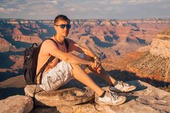 Young man sitting at the edge of the Grand Canyon. On the island of Kauai, Hawaii Royalty Free Stock Photography