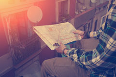 Young man sitting on the edge of high roof with map in hands. Brave young man sitting on the edge of high roof with map in hands Stock Image