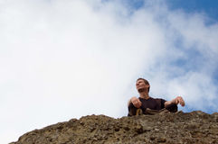 Young man sitting  at the edge of rock Royalty Free Stock Images