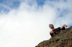 Young man sitting  at the edge of rock Stock Photos