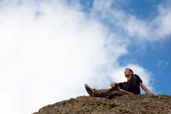 Young man sitting  at the edge of rock Stock Image