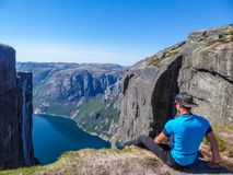 Norway - A man sitting at the egde of a steep mountain with a fjord view royalty free stock photos