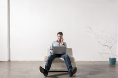 Young man sitting in empty room, using cell phone and notebook P Stock Images