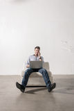 Young man sitting in empty room, using cell phone and notebook P Royalty Free Stock Image