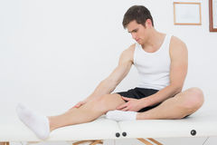 Young man sitting on examination table in medical office Royalty Free Stock Image