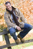 Young man sitting on fence Royalty Free Stock Photos