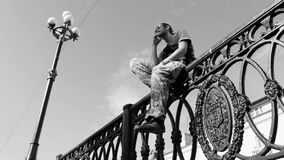 Young man sitting on the fence. Black and white stock video footage