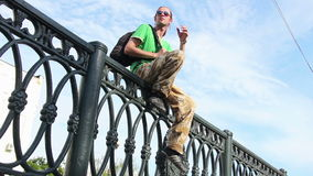 Young man sitting on the fence. stock footage