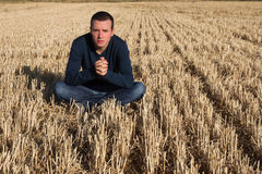 Young Man Sitting in Field Stock Images