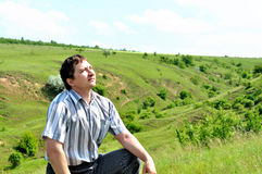 A young man sitting in a field and reflects Royalty Free Stock Photography