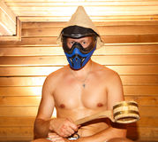 Young man sitting in Finnish bath in paintball mask. With pot in his hand Stock Photography