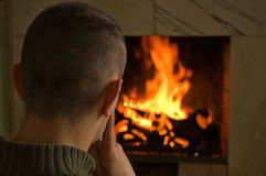 Young man sitting at fireplace royalty free stock photo