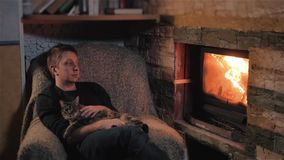 Young Man Sitting By Fireplace And Hugging Cute Cat In a Country House stock video