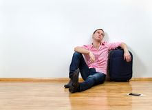 Young man sitting on the floor Stock Photos