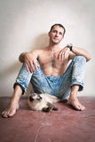 Young man sitting on the floor with his cat Royalty Free Stock Photos