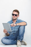 Young man sitting on the floor holding a tablet pc. A portrait of young man sitting on the floor holding a tablet pc Stock Photos