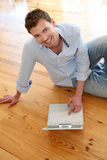 Young man sitting on the floor with laptop Royalty Free Stock Photos