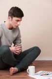 Young man sitting on floor with legs crossed. Royalty Free Stock Image