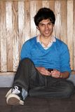 Young man sitting on floor with mobile phone Royalty Free Stock Photography