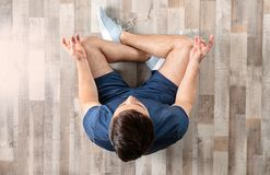 Young man sitting on floor and practicing zen yoga royalty free stock photos