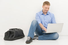 Young man sitting on floor and smiling. Stock Photos