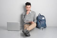 Young man sitting on the floor and using laptop. Stock Photos