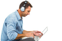 Young man sitting on floor using laptop and headphones Royalty Free Stock Images