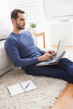 Young man sitting on floor using laptop Royalty Free Stock Images