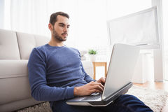 Young man sitting on floor using laptop Royalty Free Stock Photos