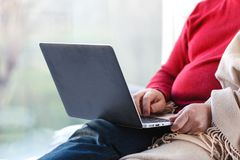 Young man sitting on floor using laptop at home in the living room Stock Photo