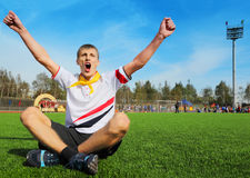 Young man sitting on football field and shouting Royalty Free Stock Images