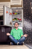 Young Man Sitting In Front Of Fridge Stock Image