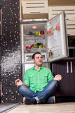 Young Man Sitting In Front Of Fridge Royalty Free Stock Photos