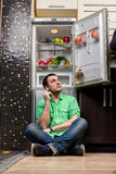 Young Man Sitting In Front Of Fridge Royalty Free Stock Image