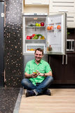 Young Man Sitting In Front Of Fridge Royalty Free Stock Photography